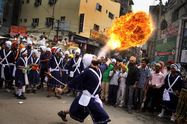 A Sikh youth performs an act of fire as he displays martial art skills during a religious procession on the eve of birth anniversary of Guru Ram Das in Amritsar, India, Tuesday, October 8, 2013. Ram Das was the fourth of the ten gurus of Sikhism. (Photo by Sanjeev Syal/AP Photo)