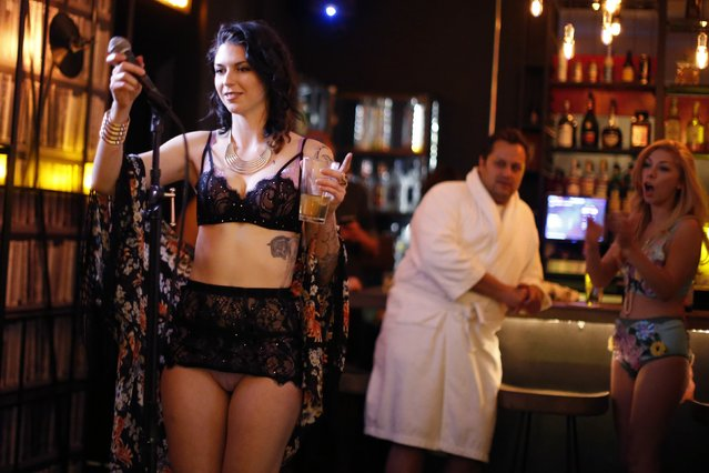 Chelsea Schaefer (L), 25, is applauded after singing at the first annual Underwear Karaoke, an event that pairs two common fears: being seen in your underwear and singing in public, in Los Angeles, California March 12, 2015. (Photo by Lucy Nicholson/Reuters)