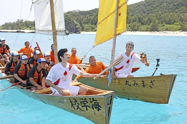 The Olympic flame is passed from torch to torch on traditional rowboats during the Tokyo 2020 Olympics torch relay off Zamami in Japan's southernmost island prefecture of Okinawa, southwestern Japan, May 2, 2021, in this photo relased by Kyodo. (Photo by Kyodo News via Reuters)