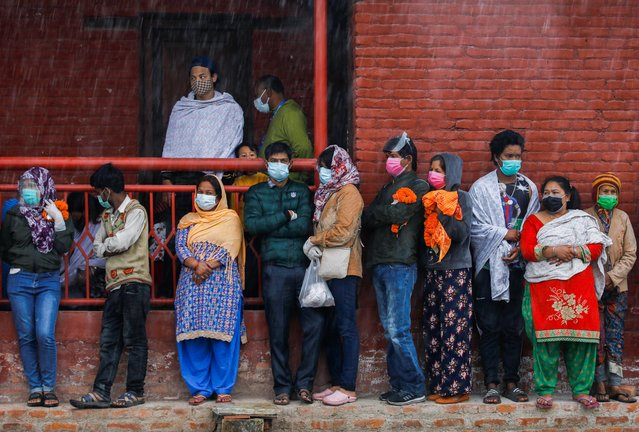 Family members stand in the rain outside the crematorium as they wait for the bodies of their relatives, who died from the coronavirus disease (COVID-19), to arrive at the crematorium, in Kathmandu, Nepal on May 11, 2021. (Photo by Navesh Chitrakar/Reuters)