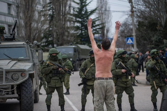 In this Saturday, March 1, 2014 file photo, a Ukrainian man stands in protest in front of gunmen in unmarked uniforms as they stand guard in balaklava, on the outskirts of Sevastopol, Crimea. (Photo by Andrew Lubimov/AP Photo)