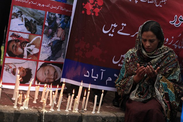 A woman from the Christian community prays next to pictures of victims of the suicide bombings in Lahore, during a protest in Islamabad March 16, 2015. The suicide bombings outside two churches in Lahore killed 14 people and wounded nearly 80 others during services on Sunday in attacks claimed by a faction of the Pakistani Taliban. (Photo by Faisal Mahmood/Reuters)