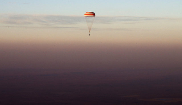 The Soyuz TMA-19M capsule carrying NASA's Jeff Williams, and Russian cosmonauts Alexey Ovchinin and Oleg Skripochka descends beneath a parachute near the town of Zhezkazgan, Kazakhstan, on September 7, 2016. The record-setting American and two Russians landed safely back on Earth after a six-month mission aboard the International Space Station. (Photo by Maxim Shipenkov/Pool Photo via AP Photo)