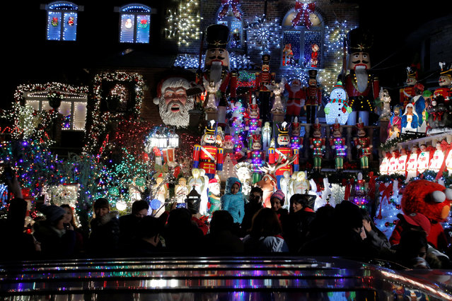 People walk by at the Dyker Heights Christmas Lights in the Dyker Heights neighborhood of Brooklyn, New York City, U.S., December 23, 2016. (Photo by Andrew Kelly/Reuters)