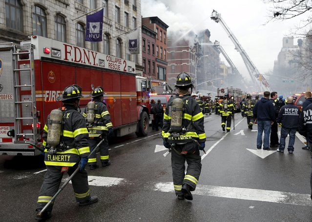 New York City Fire Department firefighters walk on 2nd Avenue towards the site of where a residential apartment was engulfed in flames in New York City March 26, 2015. (Photo by Mike Segar/Reuters)