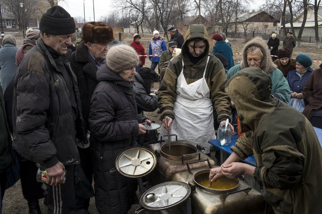 People queue for a free food distributed by pro-Russian rebels in the village of Chornukhyne near the town of Debaltseve, north-east from Donetsk, March 12, 2015. (Photo by Marko Djurica/Reuters)