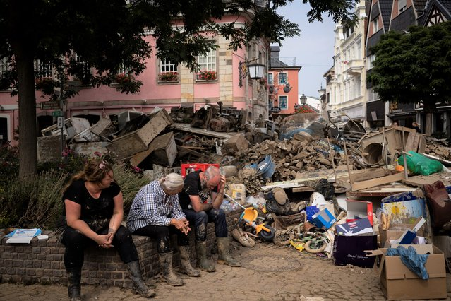 People rest from cleaning up the debris of the flood disaster in Bad Neuenahr-Ahrweiler, Germany, Monday July 19, 2021. More than 180 people died when heavy rainfall turned tiny streams into raging torrents across parts of western Germany and Belgium, and officials put the death toll in Ahrweiler county alone at 110. (Photo by Bram Janssen/AP Photo)