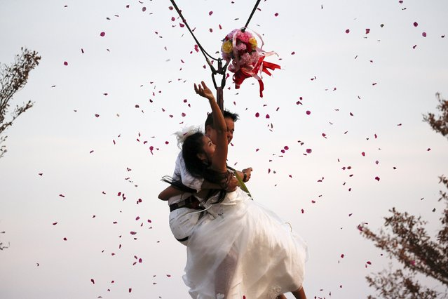 Groom David Leslie Chesterman, from England, and his bride Charunee Koydun throw a bouquet as they fly while attached to cables during a wedding ceremony ahead of Valentine's Day at a resort in Ratchaburi province, Thailand, February 13, 2016. (Photo by Athit Perawongmetha/Reuters)