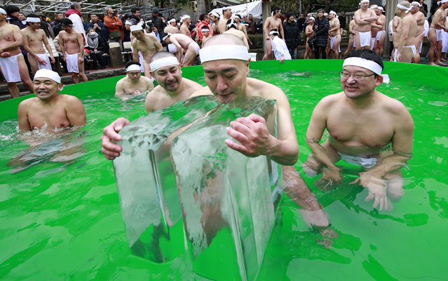 Japanese bathers pray for the healthy new year while dipping in a cold water tub with blocks of ice at a park by Teppozu Inari Shinto Shrine during a winter ritual in Tokyo, Sunday, January 8, 2017. About 100 people gathered for the mid-winter event to pray for their healthy new year and displayed their perseverance. (Photo by Shizuo Kambayashi/AP Photo)