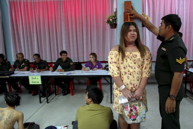 Sivakorn, a 21-year-old transgender, gets measured during an army draft held at a school in Bang Na in Bangkok, April 3, 2015. Thai men over 21 must serve in the army. Those who volunteer serve six months, but others choose the annual lottery, which goes on for 10 days in recruitment centres around Thailand. (Photo by Athit Perawongmetha/Reuters)