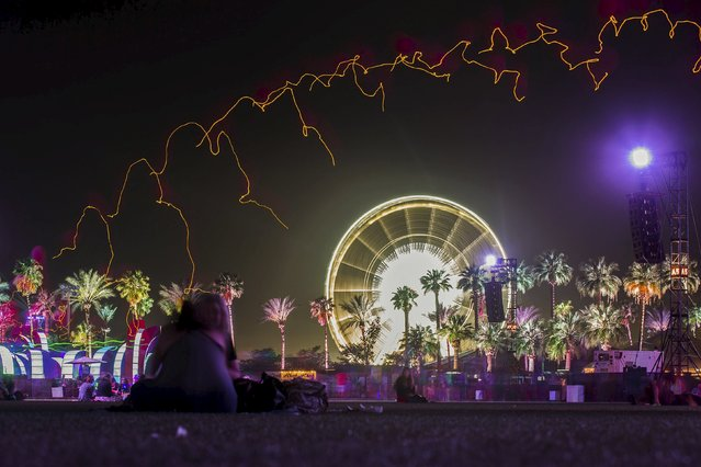 People sit under a row of lit balloons in front of a ferris wheel at the Coachella Valley Music and Arts Festival in Indio, California April 10, 2015. Picture taken with a long camera exposure. (Photo by Lucy Nicholson/Reuters)