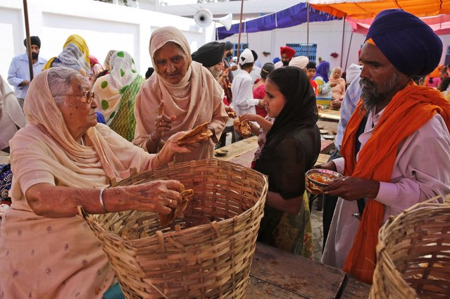An Indian Sikh woman, left distributes food to devotees at a Sikh temple on Baisakhi, in New Delhi, India, Tuesday, April 14, 2015. Baisakhi, the harvest festival celebrated in the Punjab region also coincides with other festivals celebrated on the first day of Indian calendar month Vaisakh. (Photo by Manish Swarup/AP Photo)