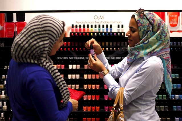 """Two Egyptian women buy """"breathable"""" nail polish from a store in a Dubai shopping mall in this November 18, 2013 file photo. The United Arab Emirates is expected to report inflation data this week. (Photo by Ahmed Jadallah/Reuters)"""