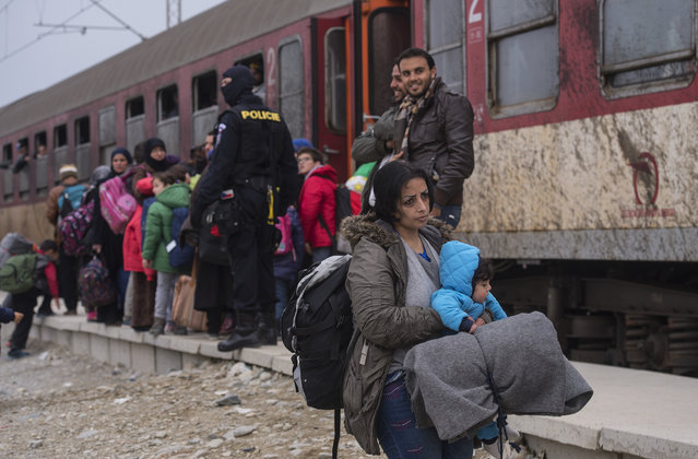 Refugees and migrants try to find a place on an already full train headed for Serbia, near the city of Gevgelija, The Former Yugoslav Republic of Macedonia, on February 24, 2016. Refugees and migrants from Iraq and Syria continue to pass through Macedonia on their way to the European Union. (Photo by Georgi Licovski/EPA)