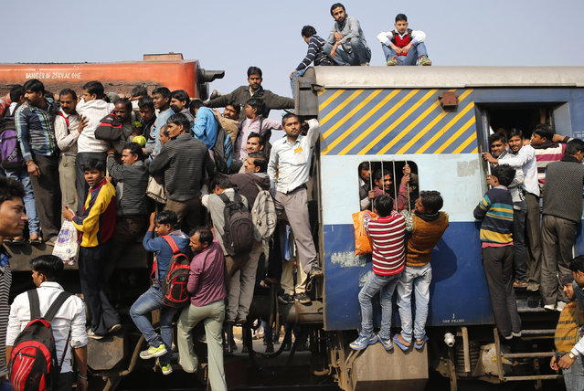 Passengers board an overcrowded train near a railway station at Loni town in the northern state of Uttar Pradesh, India, February 24, 2016. (Photo by Anindito Mukherjee/Reuters)
