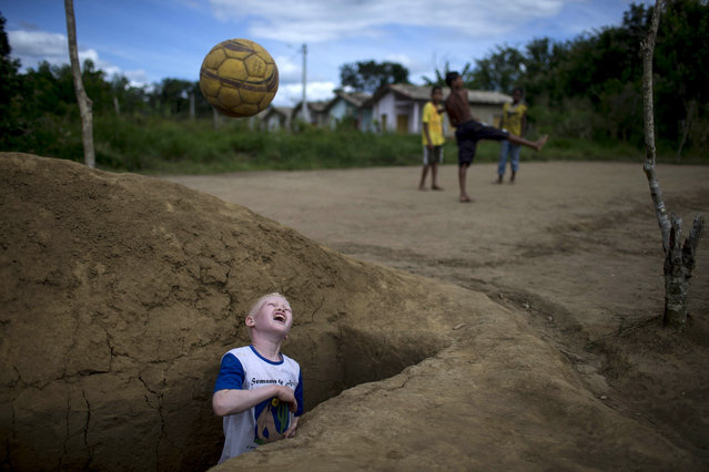 Maicon de Jesus Dias throws a ball he recovered from an open grave while playing soccer in a makeshift field in a local cemetery of the city of Una, Bahia state, Brazil, April 29, 2014. (Photo by Roosevelt Cassio/Reuters)