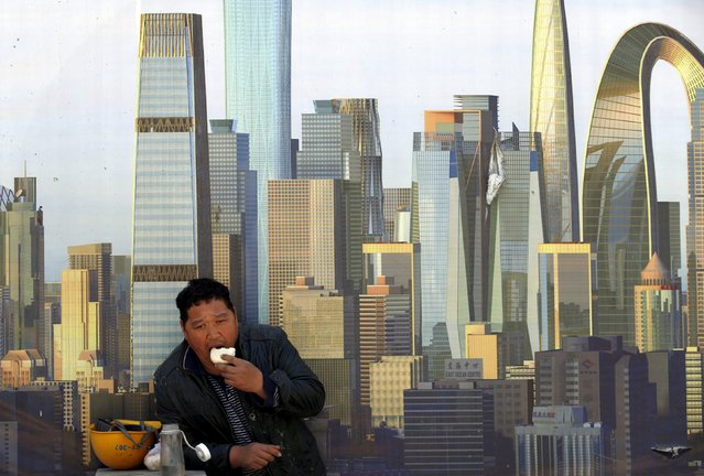 A construction worker eats a bun during a lunch break in front of a wall of a construction site in Beijing April 20,  2015. China's central bank on Sunday cut the amount of cash that banks must hold as reserves, the second industry-wide cut in two months, adding more liquidity to the world's second-biggest economy to help spur bank lending and combat slowing growth. (Photo by Kim Kyung-Hoon/Reuters)