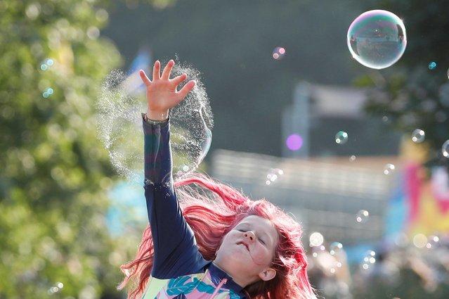 A young festivalgoer jumps to burst a bubble at Latitude Festival at Henham Park, Britain, July 22, 2021. (Photo by Peter Cziborra/Reuters)