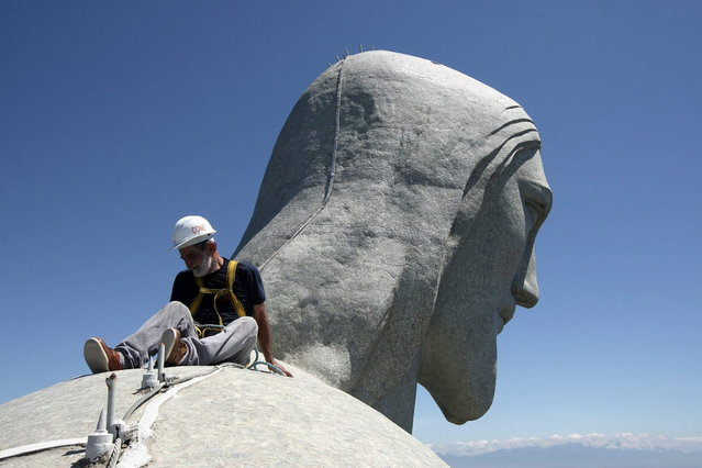 A worker inspects the Christ the Redeemer statue which was damaged during lightning storms in Rio de Janeiro January 21, 2014. (Photo by Severino Silva/Reuters/Agência o Dia)