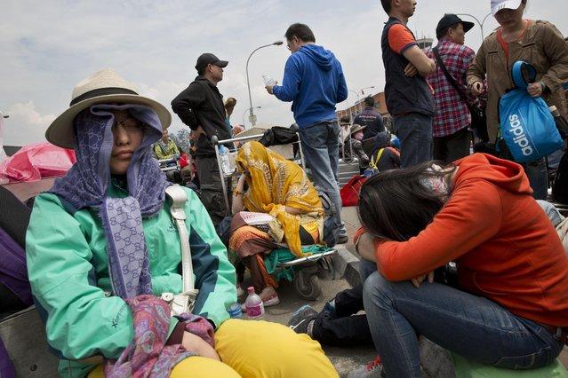 Chinese nationals gather outside the Kathmandu international airport, Sunday, April 26, 2015. (Photo by Bernat Armangue/AP Photo)