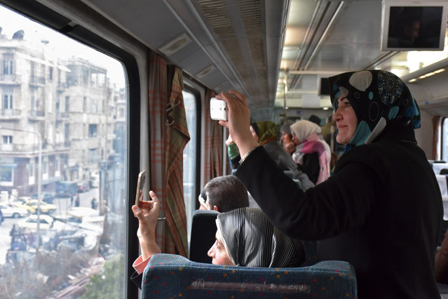 Syrian women take pictures as they ride a train travelling through Aleppo's devastated eastern districts for the first time in more than four years, on January 25, 2017. It is the train's first such trip since rebels overran east Aleppo in the summer of 2012, effectively dividing the northern city into a regime-held west and a rebel-controlled east. (Photo by George Ourfalian/AFP Photo)