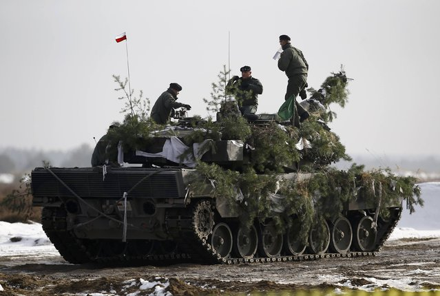 Polish army soldiers stay atop of their Leopard 2A4 tank after live firing exercise in Zagan, Poland, January 30, 2017. (Photo by Kacper Pempel/Reuters)