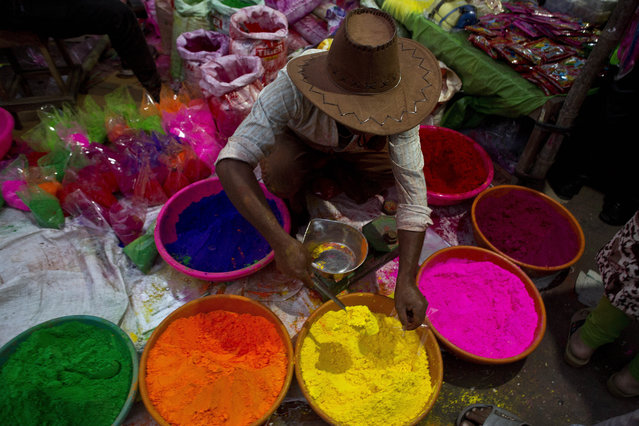 An Indian street vendor sells colored powder a day ahead of Holi, the festival of colors, in Gauhati, India, Wednesday, March 20, 2019. Holi also marks the advent of Spring season. (Photo by Anupam Nath/AP Photo)