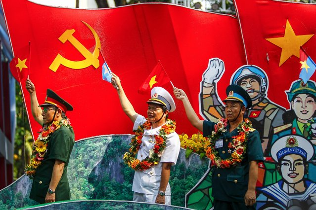 Vietnamese veterans wave flags during a parade marking the 40th anniversary of the end of the Vietnam War in Ho Chi Minh City, Vietnam, 30 April 2015. On 30 April 1975, North Vietnamese troops poured into Saigon, now called Ho Chi Minh City, for the final day of a two-decade conflict which had divided a nation, the end of the conflict coming two years after the United States withdrew its troops under the Paris Peace Accords. (Photo by Le Quang Nhat/EPA)