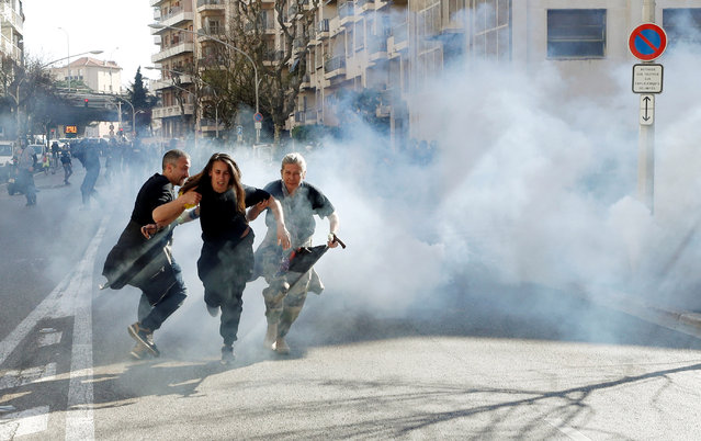 """Protesters run away as tear gas is fired during 19th round of """"yellow vests"""" protests in Nice, France, March 23, 2019. (Photo by Eric Gaillard/Reuters)"""
