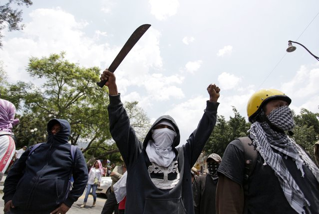 A protester holds up a machete during a march for Labour Day in Chilpancingo, Mexico May 1, 2015. (Photo by Daniel Becerril/Reuters)