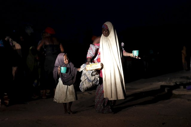 A girl and her mother rescued from Boko Haram in Sambisa forest by Nigeria Military seen with some food as they arrives at the Internally displaced people's camp in Yola, Adamawa State, Nigeria, May 2, 2015. (Photo by Afolabi Sotunde/Reuters)