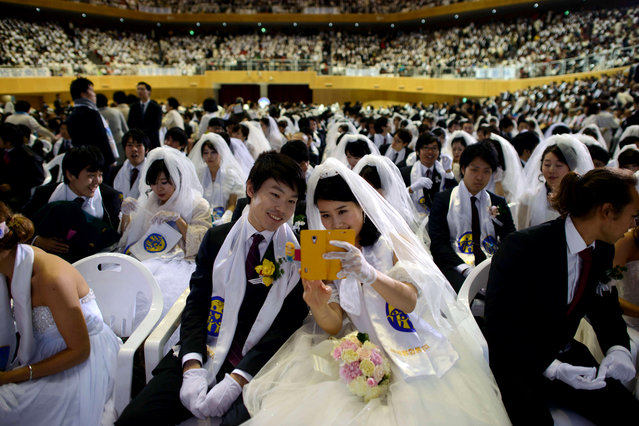 """A couple pose for a photo prior to a mass wedding at an event held by the Unification Church in Gapyeong on February 12, 2014. Unification Church members forming 2500 couples from 52 countries were married in a mass wedding in South Korea – only the second such event since the death of their """"messiah"""" and controversial church founder Sun Myung Moon."""