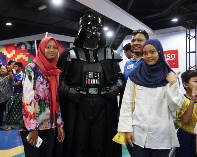 Malaysians poses for a souvenir photograph with a Star Wars fan, center, dressed as Darth Vader in a mall downtown Kuala Lumpur, Malaysia, Saturday, May 2, 2015. (Photo by Joshua Paul/AP Photo)