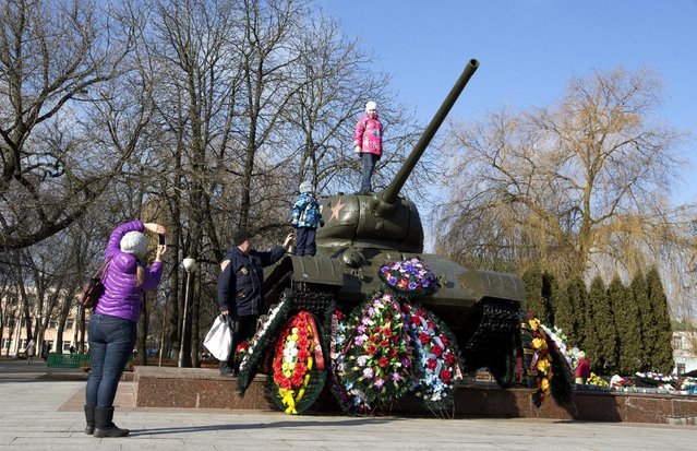 A girl poses for a photo as she stands on a T-34 tank, a World War Two monument, in the town of Bobruisk, southeast of Minsk, March 7, 2015. Belarus will mark Victory Day on May 9, the 70th anniversary of the Soviet Union's victory over Nazi Germany. (Photo by Vasily Fedosenko/Reuters)