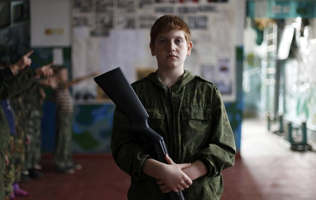 A boy takes part in military training undergone by students of the General Yermolov Cadet School and members of a local youth military patriotic club at a boot camp of the Russkiye Vityazi (Russian Knights) military patriotic club in the village of Sengileyevskoye outside Stavropol, Russia, November 2, 2016. (Photo by Eduard Korniyenko/Reuters)