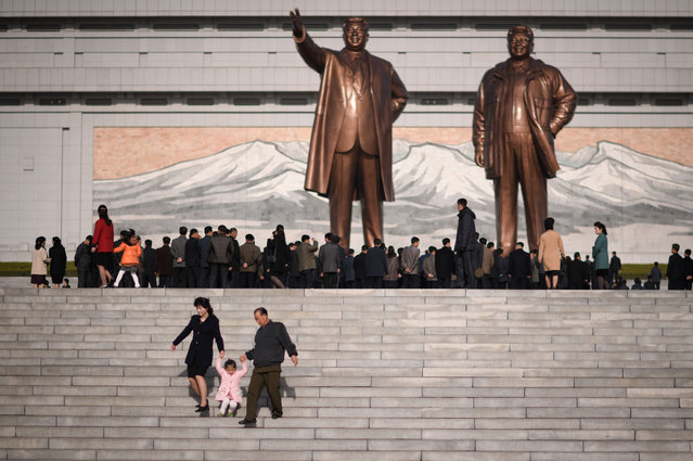 "A family walk down steps after paying their respects before the statues of late North Korean leaders Kim Il Sung and Kim Jong Il, as part of celebrations marking the anniversary of the birth of Kim Il Sung, known as the ""Day of the Sun"", on Mansu hill in Pyongyang on April 15, 2019. (Photo by Ed Jones/AFP Photo)"