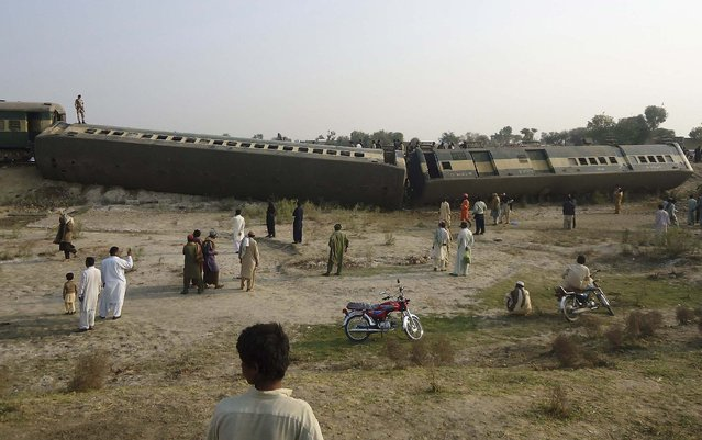 People gather at the site where a passenger train derailed after a blast in Pakistan's southern Kashmore district February 16, 2014. At least five passengers, including four children, were killed after a bomb derailed the moving train, according to the police. The train was on its way to the northwestern city of Peshawar from the southern port city of Karachi. (Photo by Abid Rehman/Reuters)