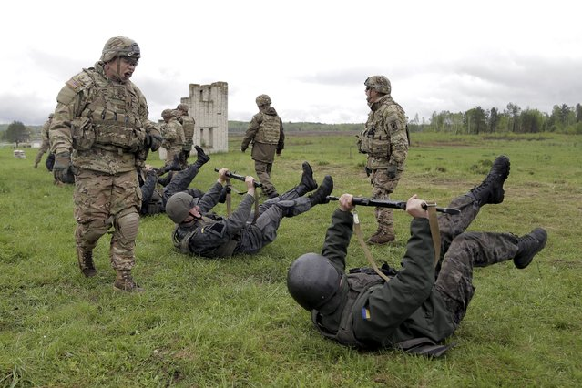 "Servicemen of the U.S. Army's 173rd Airborne Brigade Combat Team (standing) train members of the Ukrainian National Guard during a joint military exercise called ""Fearless Guardian 2015"" at the International Peacekeeping and Security Center near the western village of Starychy, Ukraine, May 7, 2015. (Photo by Roman Baluk/Reuters)"