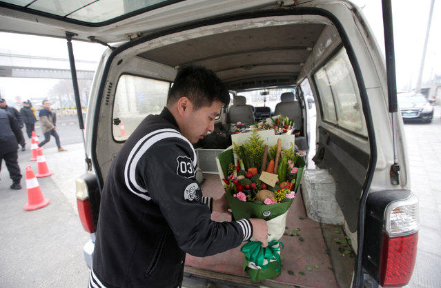 A staff member of a florist takes out a bouquet made of vegetables and flowers, priced at 238RMB, as he delivers it for a client outside an office building on Valentine's Day in Beijing, China, February 14, 2017. (Photo by Jason Lee/Reuters)