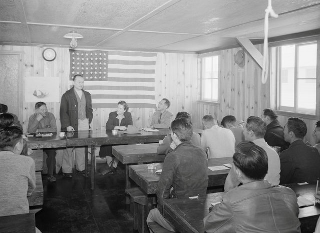 Roy Takeno stands behind a table addressing a town hall meeting with an American flag on the wall behind him at the Manzanar War Relocation Center in California, in this 1943 handout photo. (Photo by Courtesy Ansel Adams/Library of Congress, Prints and Photographs Division/Reuters)