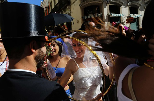 A reveler dressed as a bride holds giant wedding rings at the Boitata block party, a pre-Carnival celebration in Rio de Janeiro, February 23, 2014. (Photo by Leo Correa/Associated Press)