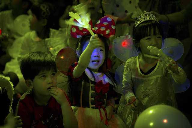 Children cheer while watching a magic show at a Mother's Day-themed disco dance party for children in Beijing, Sunday, May 10, 2015. Although not an official holiday, observance of Mother's Day is growing in China, a society that traditionally values filial piety. (Photo by Mark Schiefelbein/AP Photo)