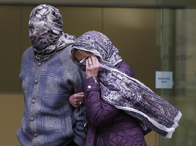 Domenico Rancadore (L) and his wife Anne Skinner cover their faces as they leave after an extradition hearing at Westminster Magistrates Court in central London March 17, 2014. A fugitive Sicilian mafia member arrested in Britain last year after living a quiet, suburban life for two decades will not be extradited back to Italy, a London court ruled on Monday. (Photo by Olivia Harris/Reuters)