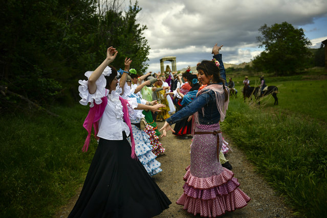 "Devotees of the Rocio Virgin dance while taking part in the ""Romeria de El Rocio"" in the countryside outside Fitero, northern Spain, Saturday, May 25, 2019. (Photo by Alvaro Barrientos/AP Photo)"