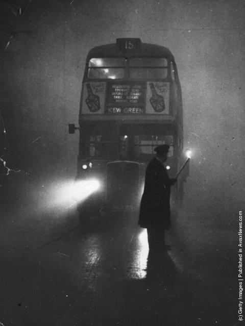 A man guiding a London bus through thick fog with a flaming torch, 1952