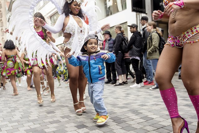 A child is seen next to a dancer at the Copenhagen Carnival parade May 23, 2015. (Photo by Jens Astrup/Reuters/Scanpix Denmark)
