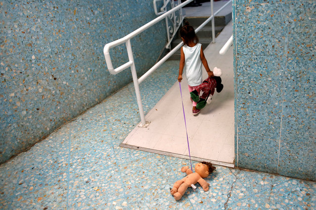 """A Central American child plays on a hallway of the Catholic shelter """"San Francisco Javier Church"""", which gives temporary shelter to asylum-seekers from Central America countries released by ICE and U.S. Customs and Border Protection (CBP) due to overcrowded facilities, in Laredo, Texas U.S. June 4, 2019. (Photo by Carlos Jasso/Reuters)"""