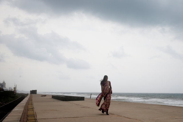 A woman walks along a railway station platform at the ocean front as rain clouds gather over Colombo, Sri Lanka on April 30, 2019. (Photo by Thomas Peter/Reuters)
