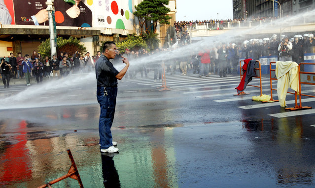 A protester refuses to leave the street despite being hit by police water cannon near the Cabinet compound in Taipei, Taiwan, March 24, 2014. Students' scuffle with police left 137 people injured. The students' protest against a controversial trade pact with China escalated on March 23 after President Ma Ying-jeou rejected students' demands, resulting in the students – who had occupied the parliament for five days – to occupy the Cabinet compound. (Photo by David Chang/EPA)
