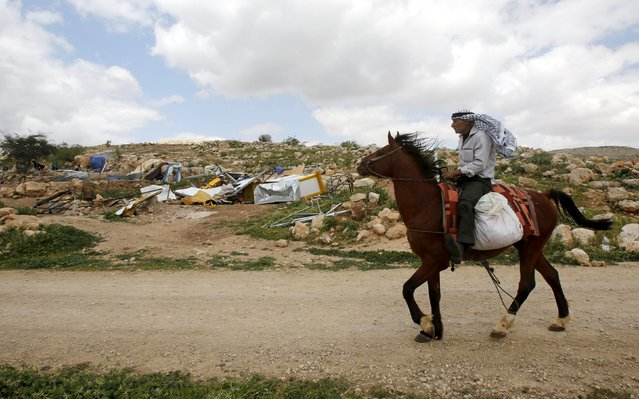 A Palestinian man rides his horse past the remains of a school that was funded by the European Commission Humanitarian Aid and Civil Protection (ECHO) and was demolished by Israeli forces, in Khirbet Tana near the West Bank city of Nablus March 29, 2016. (Photo by Abed Omar Qusini/Reuters)